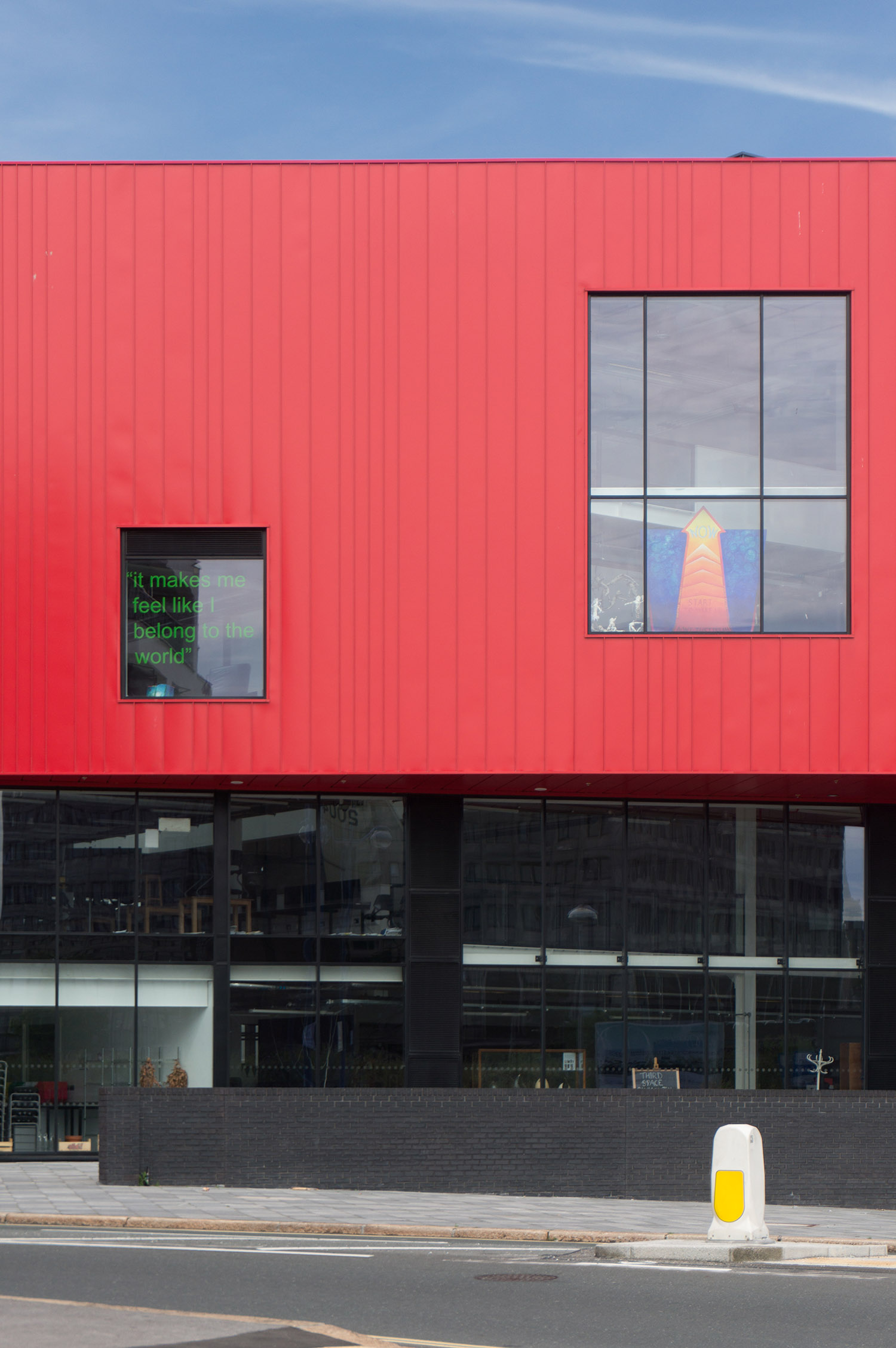 Close up view of the elevation, with industrial red steel cladding sitting above a glass and black brick plinth